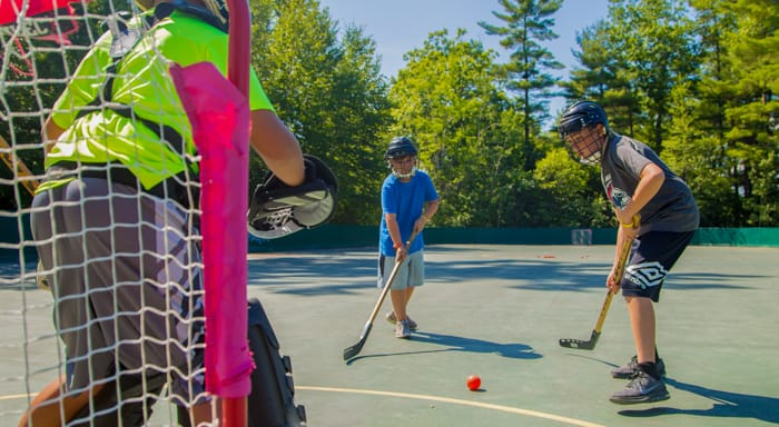 Male campers playing hockey