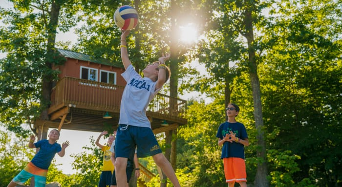 Camper spiking a volleyball