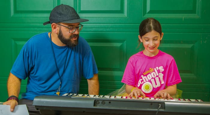Music instructor teaching keyboard to camper