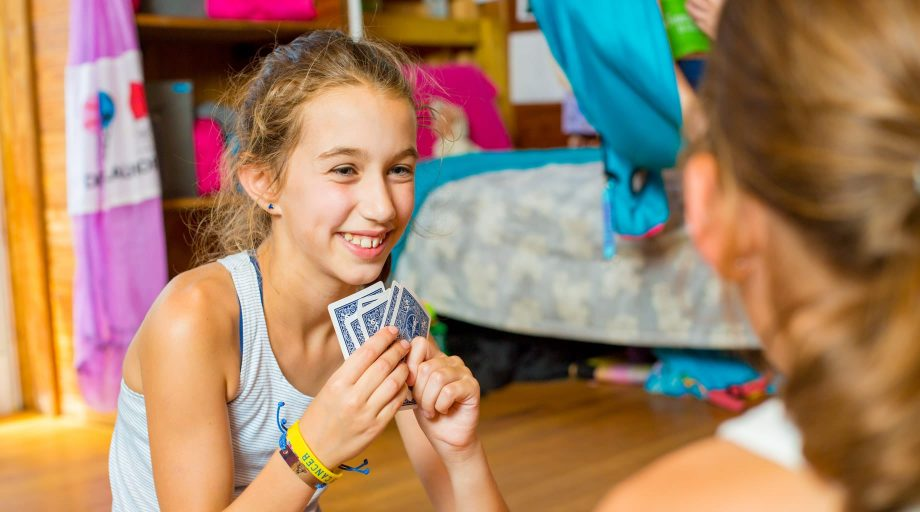 Young camper playing cards in bunk