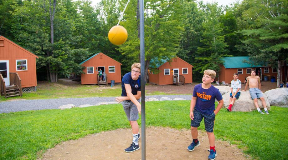 Campers playing tetherball by bunks