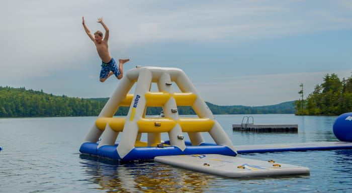 Camper jumping off waterfront inflatable into lake
