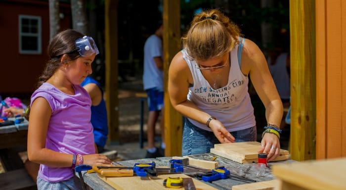 Staff helping camper with woodworking project